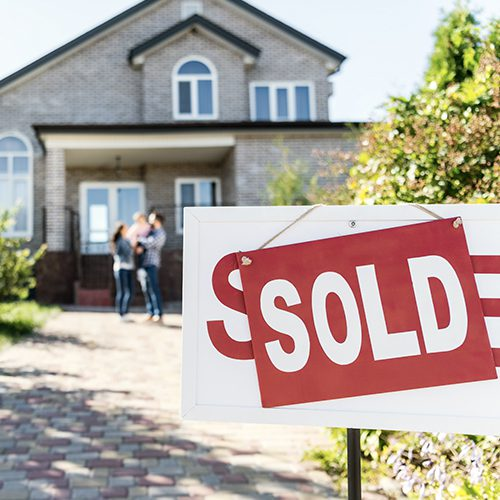 Image of family standing by a sold house sign