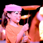 A young girl performs on stage