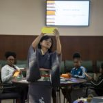 A woman teaches origami to middle school students