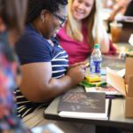 Teachers talk together at a table with art supplies